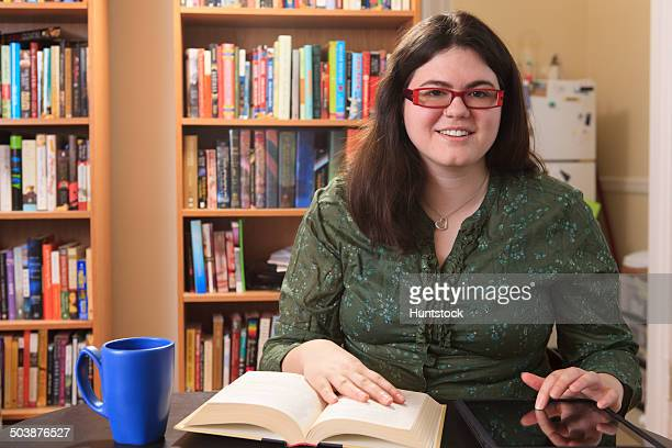 Woman with Asperger syndrome relaxing with a mug of tea and a book