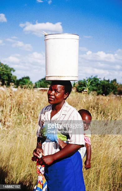 Woman with baby balancing bin on her head, Epworth Balancing Rocks.