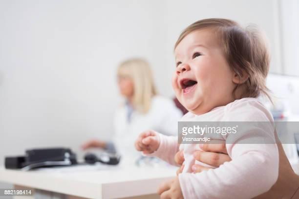 Frau mit Babymädchen in Arztpraxis