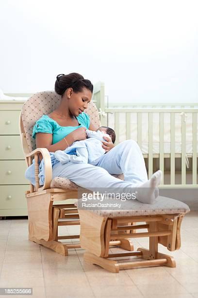 Frau mit baby in einen Schaukelstuhl.