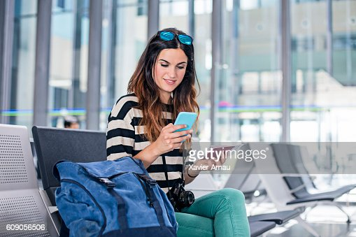 Woman with backpack and mobile phone waiting for boarding