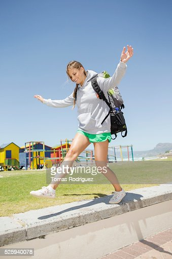 Woman with backpack balancing on stone wall : Stock Photo