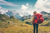 Woman with backpack enjoying mountains landscape view hiking Travel Lifestyle concept adventure vacations outdoor