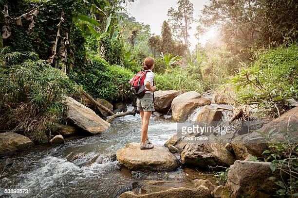 Woman with backpack hiking at rainforest river