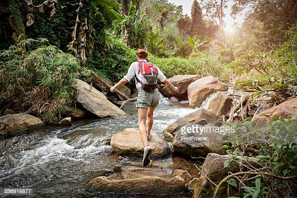 Woman with backpack hiking in rainforest