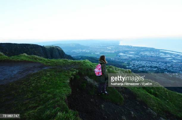 Woman With Backpack Standing On Cliff Against Sky