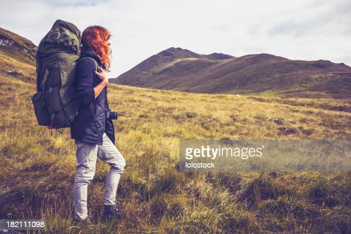 Woman with backpack trekking through the wilderness : Stock Photo