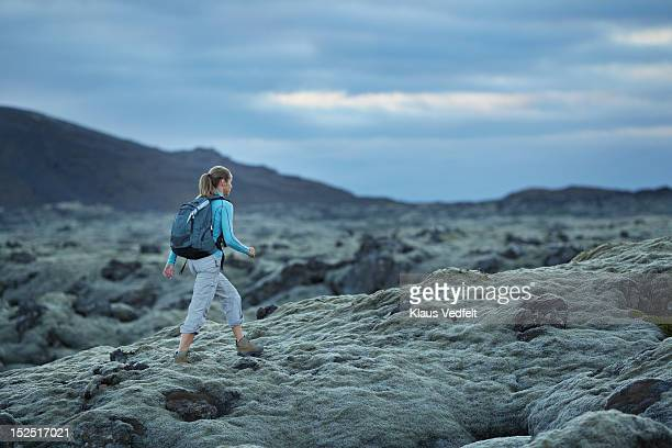 Woman with backpack walking threw lava landscape