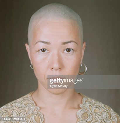 Woman with bald head and earrings, posing in studio, portrait