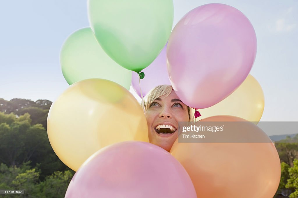 Woman with balloons circling head, smiling : Stock Photo
