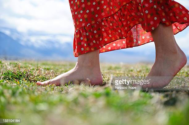 Woman with bare feet walking through field