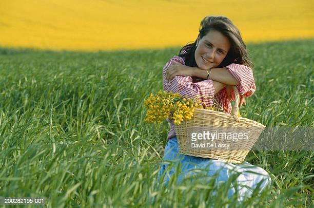 Woman with basket of flower in field