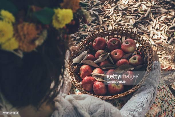 Femme avec panier rempli de pommes rouges