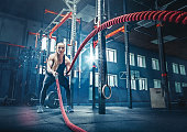 Woman with battle rope battle ropes exercise in the fitness gym.. gym, sport, rope, training, athlete, workout, exercises concept