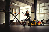 Woman training with battle ropes in gym.