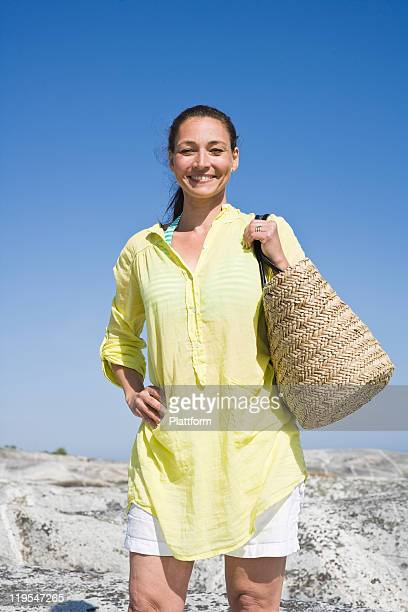 Woman with beach bag smiling, portrait