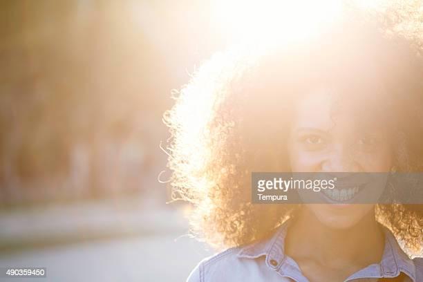 Bella donna con afro guarda alla macchina fotografica.