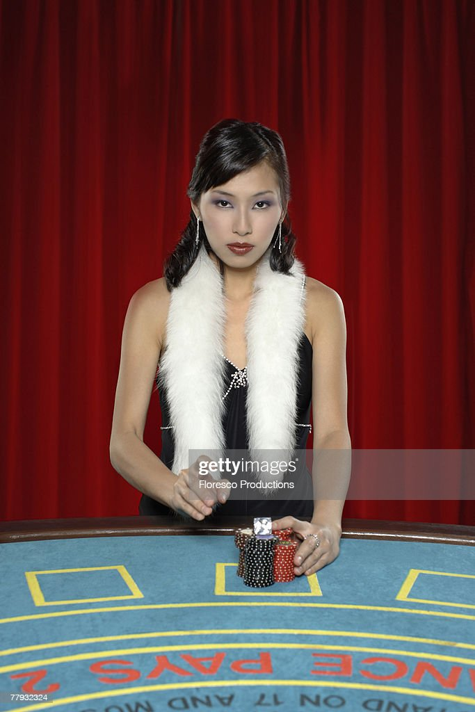 Woman with betting chips at casino table : Stock Photo