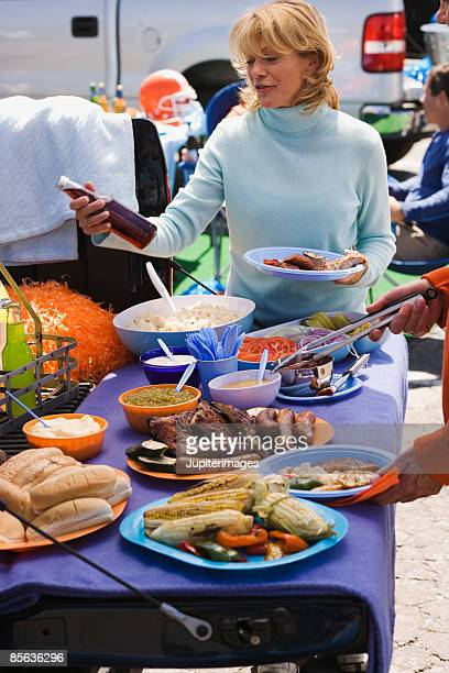 Woman with beverage and food at tailgate party