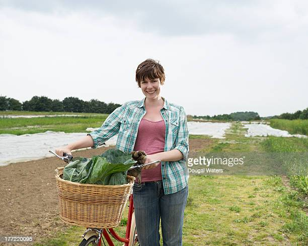 Woman with bicycle and fresh vegetables.
