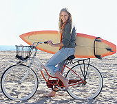 Woman with bicycle and surfboard on beach