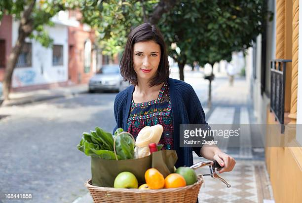 woman with bicycle basket full of fresh groceries
