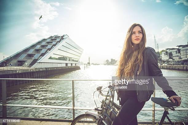 Mujer con bicicleta por el puerto