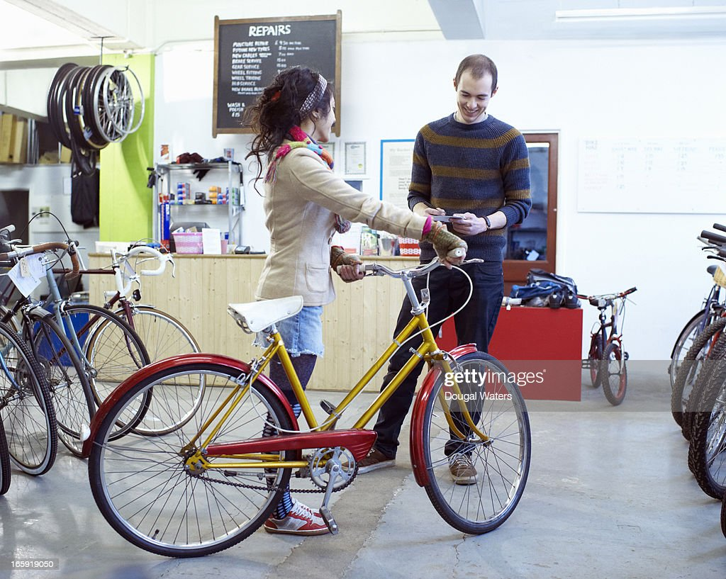 Woman with bicycle in bike shop. : Stock Photo