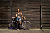 Horizontal shot of young latin woman with a bicycle standing over a wood fence.