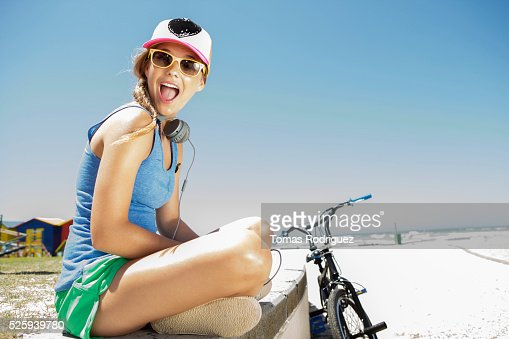 Woman with bicycle sitting on beach : Stock Photo
