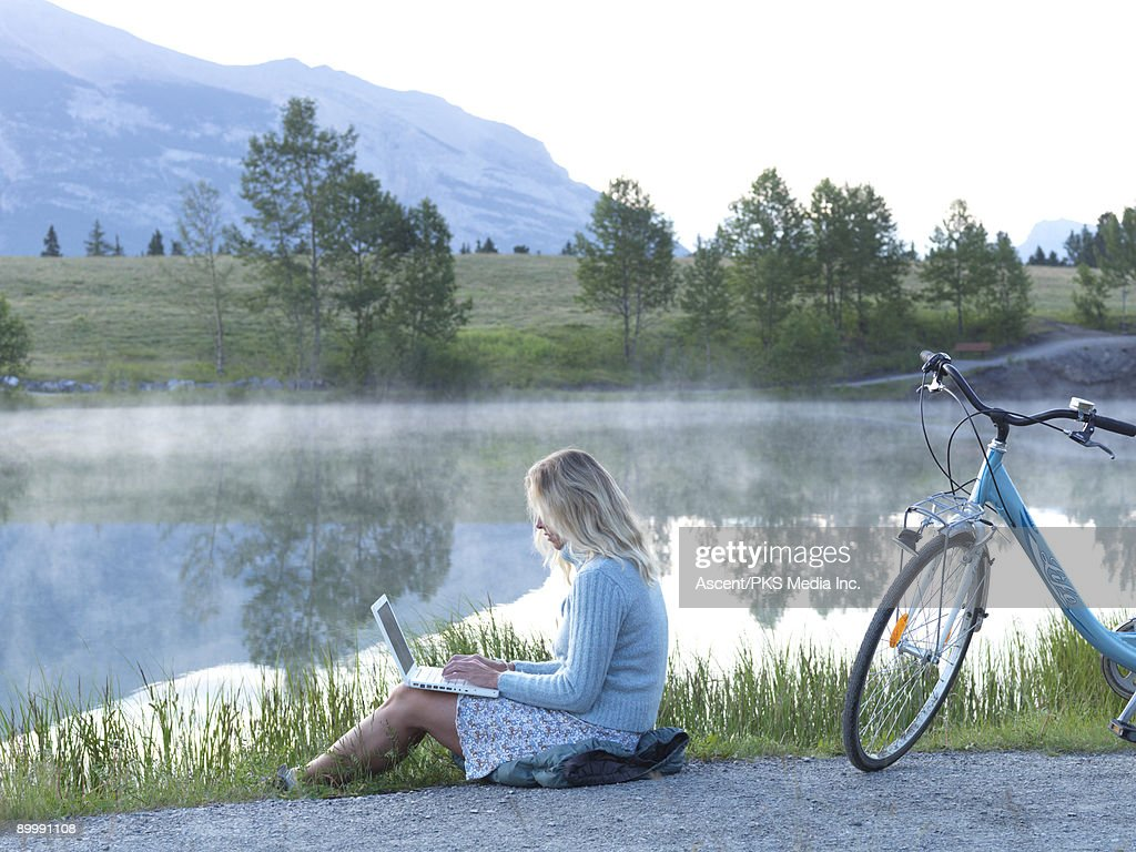 Woman with bicycle works on laptop computer, lake : Stock Photo