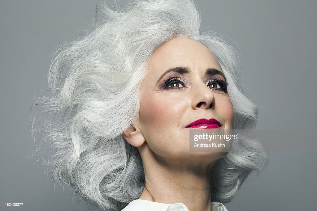 Woman with big grey hair looking up, portrait. : Stock Photo