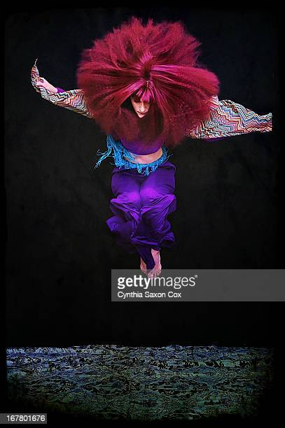 Woman with big hair jumping