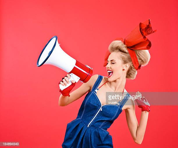 Woman with big hair ribbon shouting into megaphone