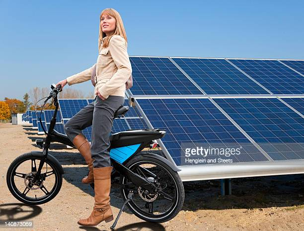 Woman with bike and solar panels