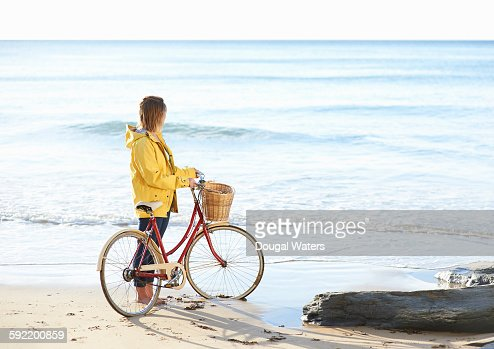 Woman with bike and yellow rain coat at beach. : Stock Photo