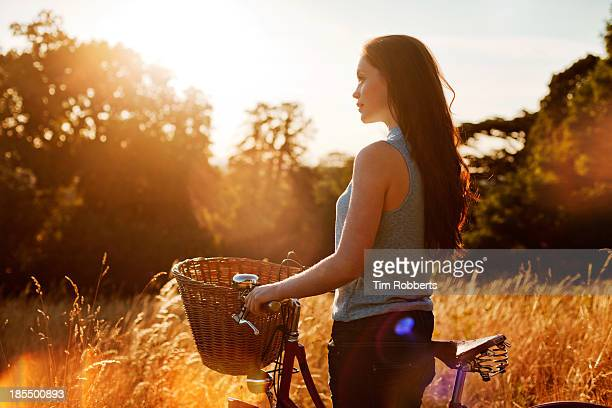 Woman with bike in field at sunset.