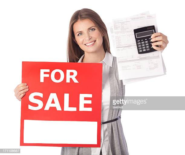Woman with bills and FOR SALE sign.