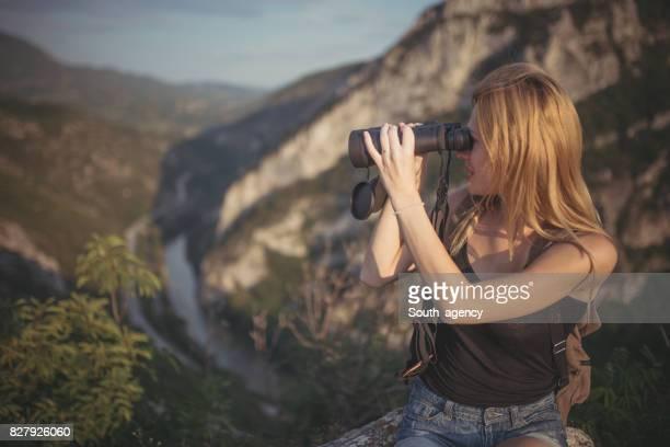 Frau mit dem Fernglas auf dem Berg