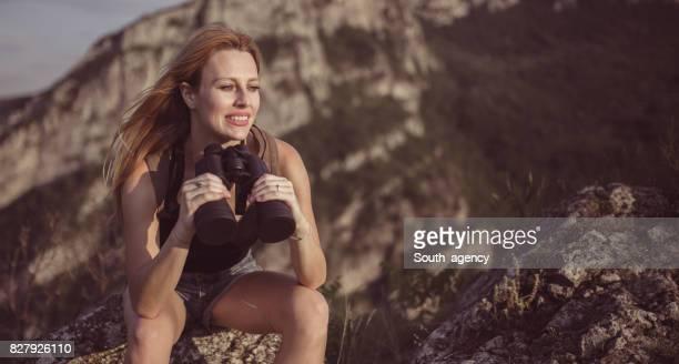 Frau mit dem Fernglas auf dem Gipfel des Berges