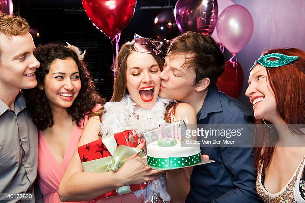 Woman with birthday cake being kissed by boyfriend