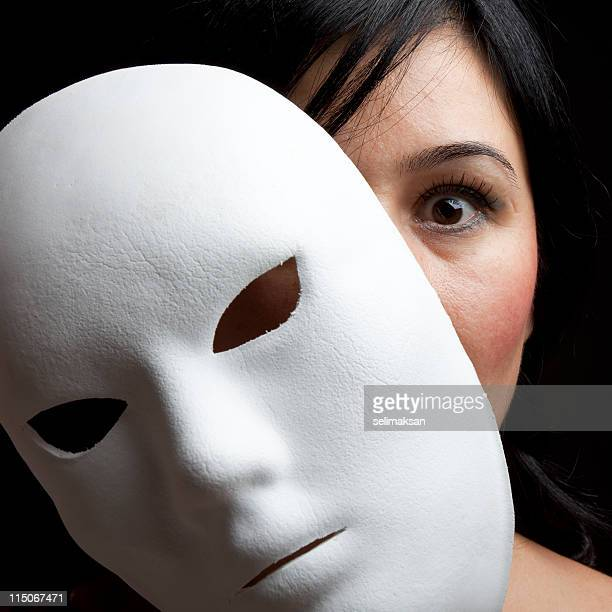 Woman With Black Hair And Eyes Peeking Behind White Mask