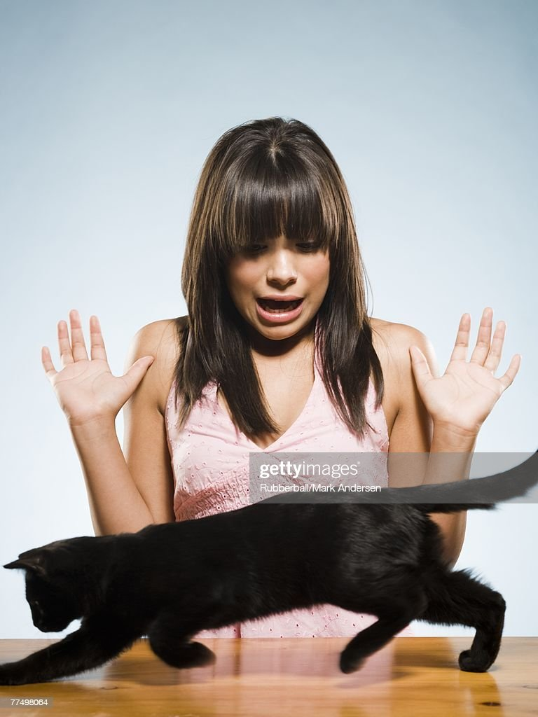 Woman with black kitten scared