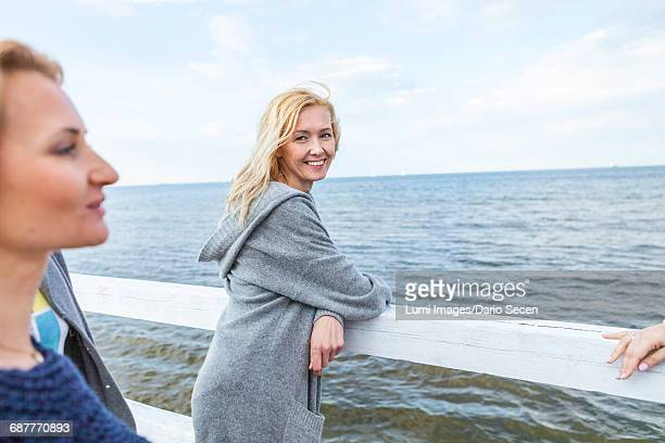Woman with blond hair and girlfriends looking at sea
