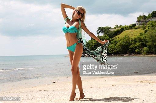 woman with blond hair in bikini relaxing on beach : Stock Photo