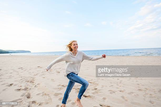 Woman with blond hair running along the beach