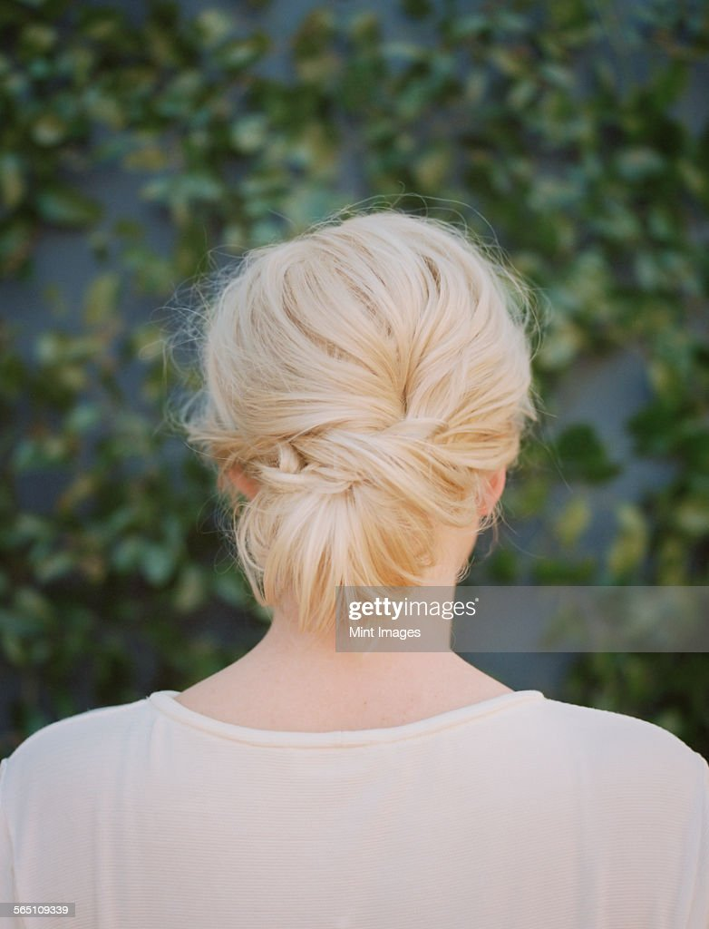 A woman with blonde hair arranged in a knot at the nape of her neck.