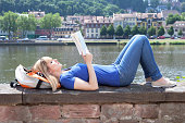 Woman with blonde hair reading a book outside on the riverside with the river and cityscape in the background