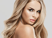 Woman beauty skin care close up portrait blonde hair studio on gray