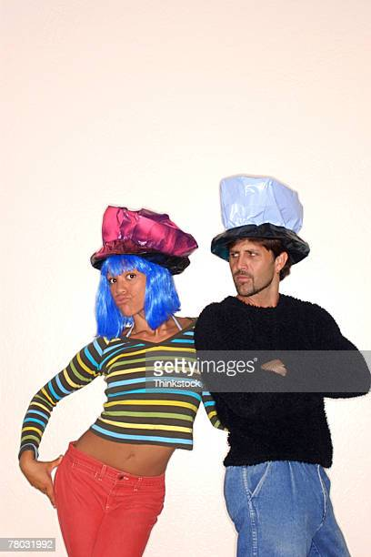A woman with blue hair ,a crumpled pink hat and a striped shirt leans on a man with a crumpled black and white hat.